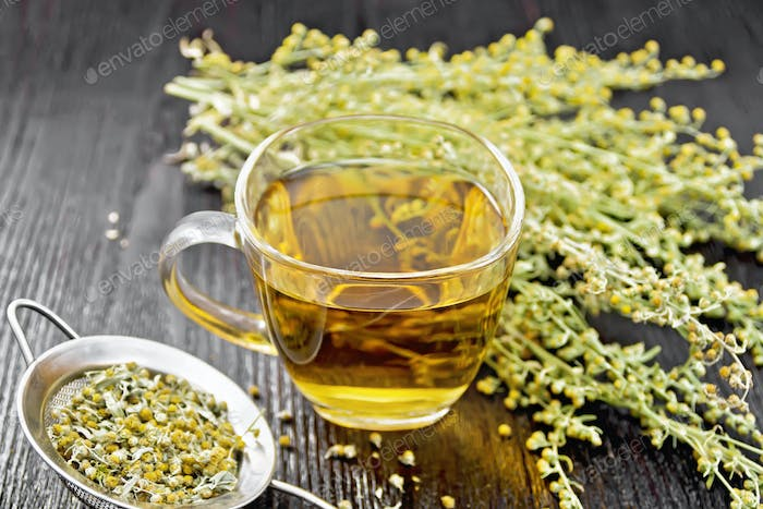 Tea of gray wormwood in glass cup with strainer on wooden board