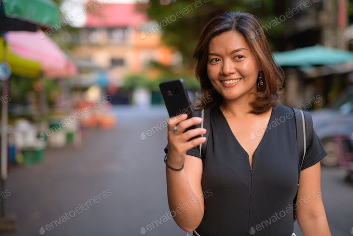 Young happy Asian tourist woman thinking while using phone in the streets