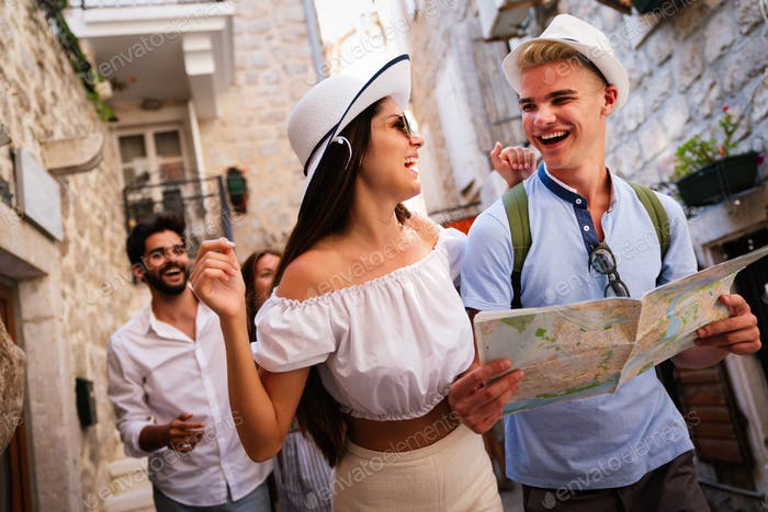 Travel, vacation and friendship concept. Group of smiling friends with city map exploring city
