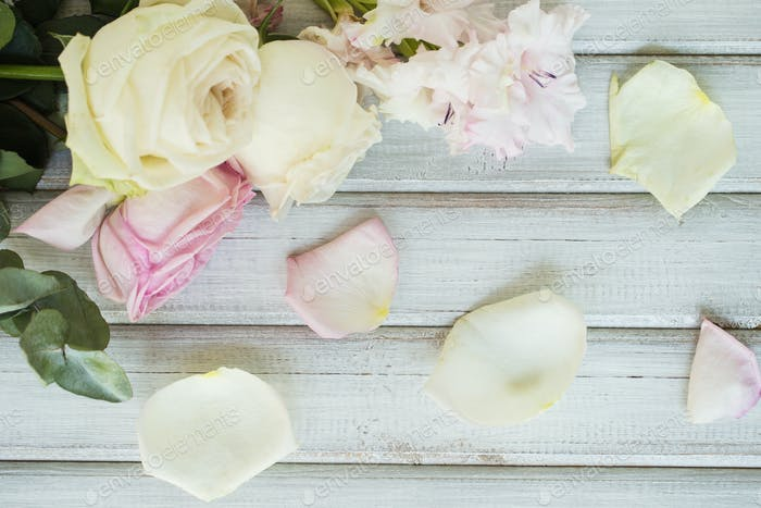 White and pink roses flowers on white painted wooden background. Selective focus. Place for text.