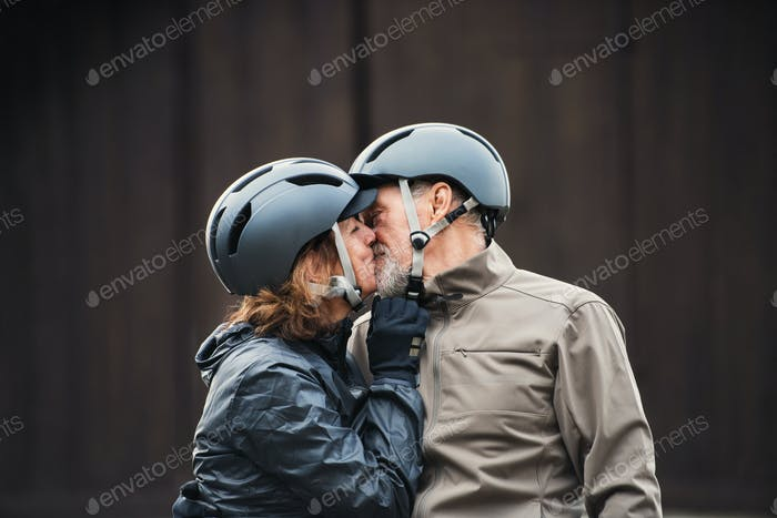 Active senior couple with bike helmets standing outdoors againts dark background, kissing.