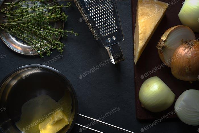 Zutaten für Zwiebelsuppe auf grauem Stein