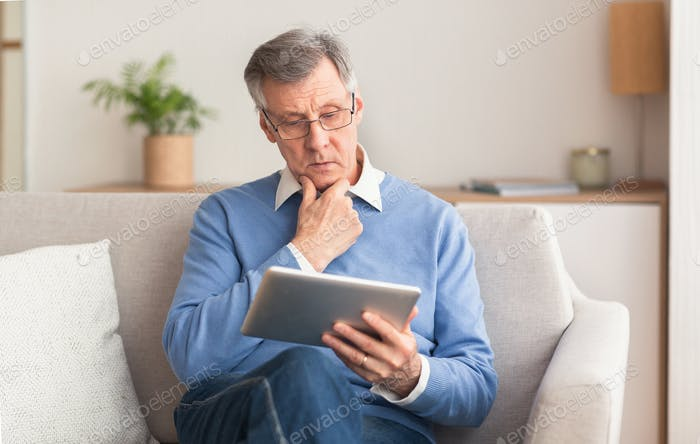 Serious Elderly Gentleman Using Tablet Sitting On Couch At Home