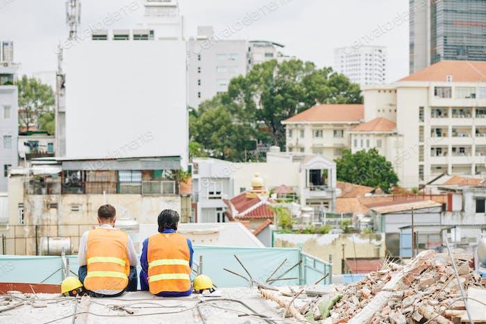 Builders looking at city