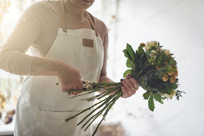 Female florist standing in her shop trimming a bouquet