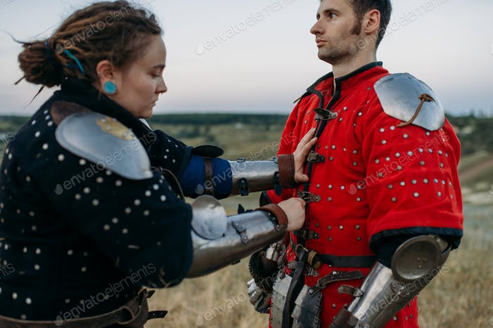 Medieval knight helps his friend to put on armor