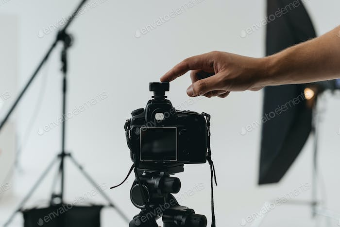 cropped view of professional photographer with digital photo camera on tripod in photo studio