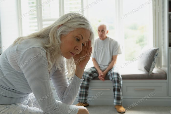 Front view of active senior Caucasian couple ignoring each other in bedroom at home