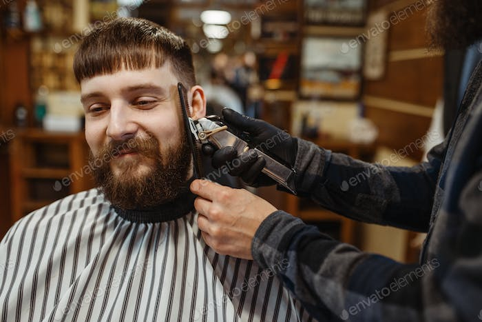 Barber with comb and clipper makes a haircut