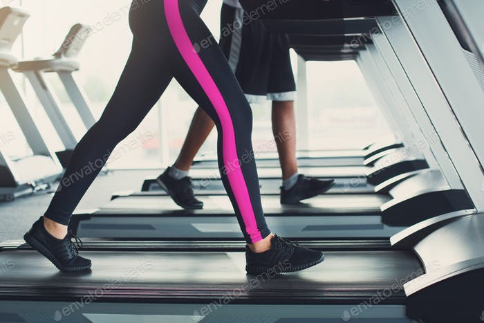 Woman's legs on treadmill in fitness club, healthy lifestyle