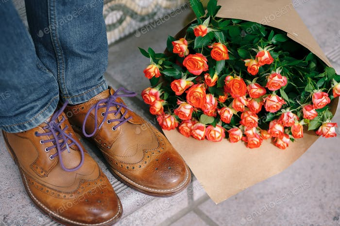 Close-up of vintage shoes with purple laces and a bouquet of ros