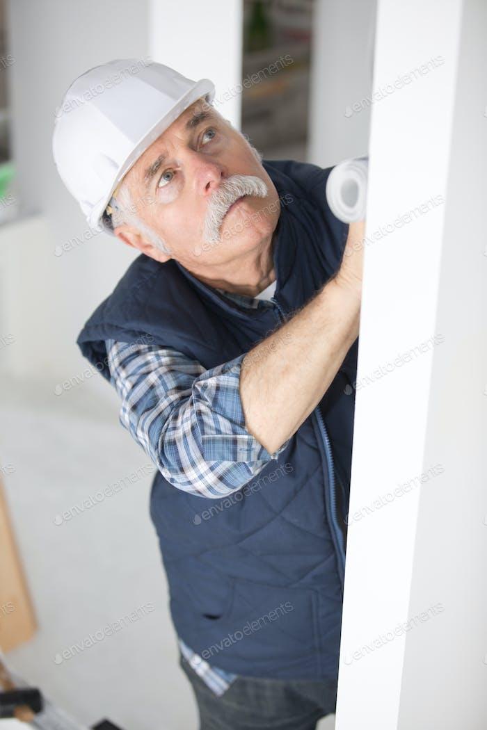 Senior worker using roller on wall