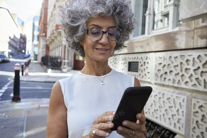 Middle aged woman using smartphone in city street, close up
