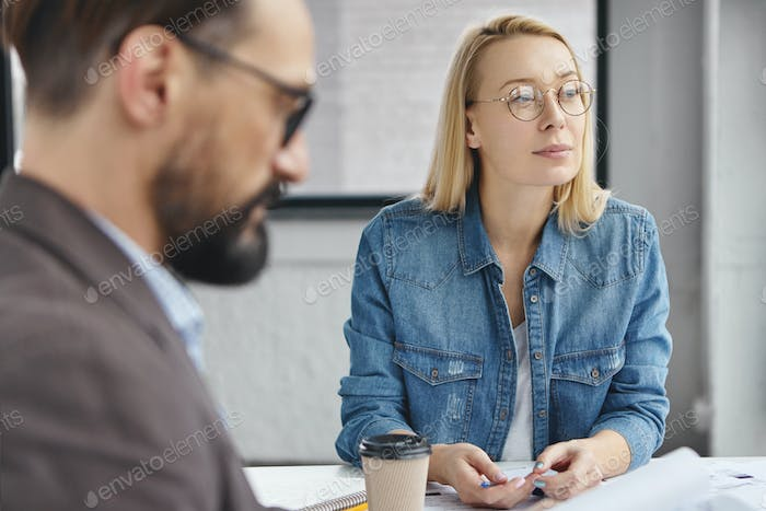 Thoughtful beautiful blonde woman in round spectacles and denim shirt sits with his boss, work toget