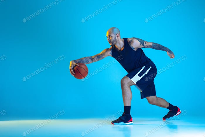 Young basketball player training isolated on blue studio background in neon light