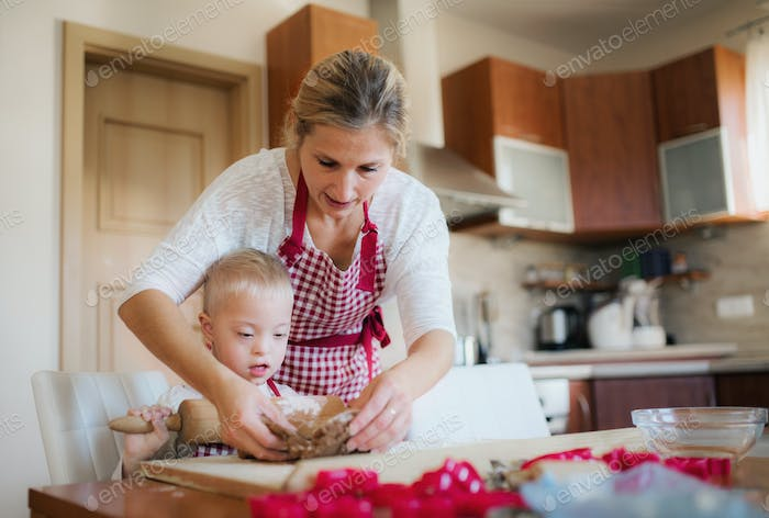 A handicapped down syndrome boy with his mother indoors baking.