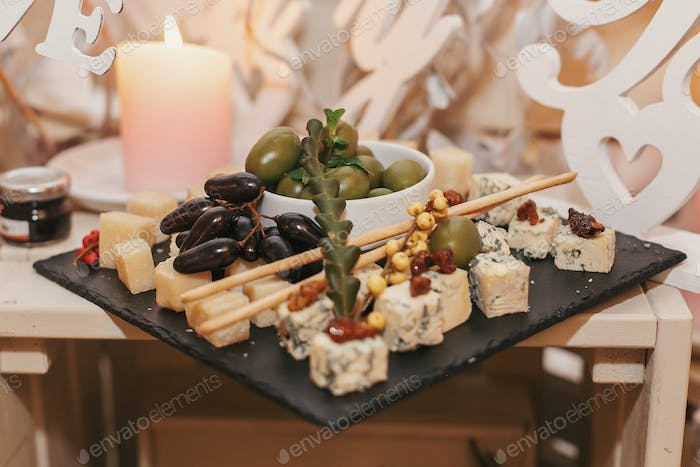 table with parmesan, gorgonzola, brie and olives and grapes