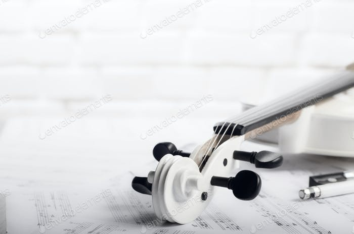 Close view of a violin and musical notes near white brick wall