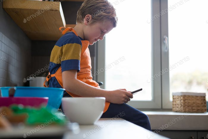 Boy using digital tablet at kitchen counter