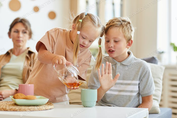 Girl with Down Syndrome Pouring Tea for Family