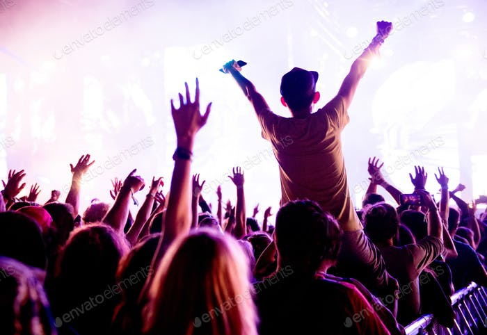 Silhouette of concert crowd in front of bright stage lights