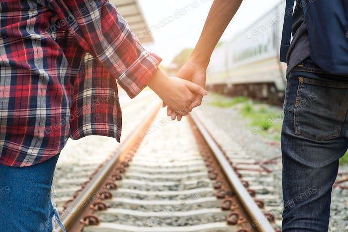 Männliche und weibliche Touristen gehen Hand in Hand auf Bahngleisen.