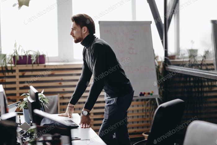 El chico vestido con ropa de oficina casual se encuentra en el escritorio en la oficina Moderno equipada con