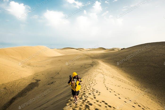 Adventurer lonely hiker in sand desert with infinite in background - sandy dunes