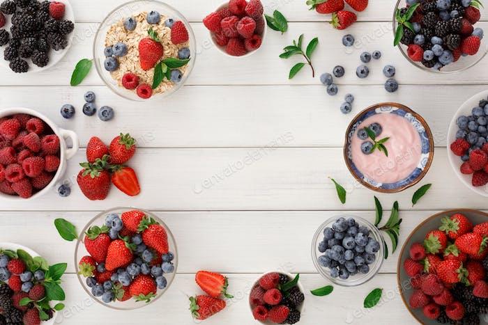 Gesundes Frühstück mit Beeren und Joghurt auf weißem Holztisch