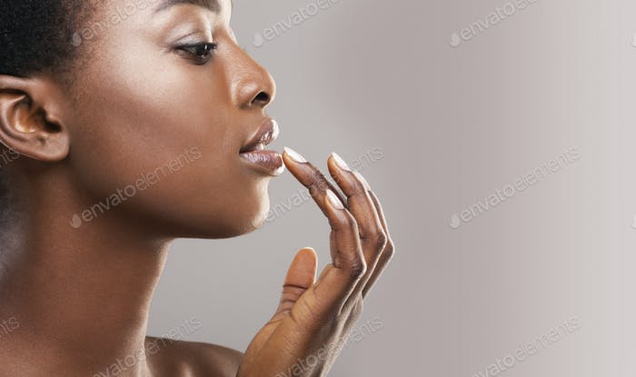 Profile portrait of beautiful african american girl touching her lips
