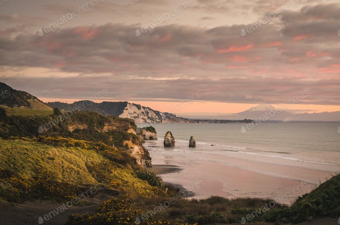 sunset over sea shore rocks and mount Taranaki, New Zealand