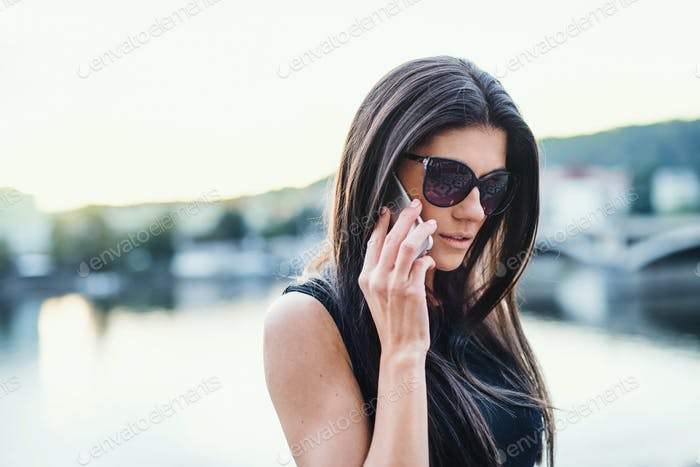 Beautiful woman in black dress standing by a river in city of Prague, making a phone call.