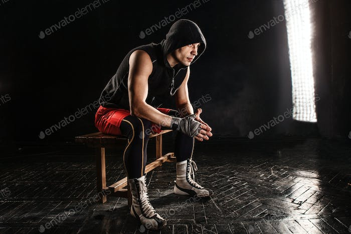 The muscular man sitting and resting on black