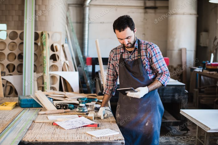 Portrait of a carpenter standing in his woodwork studio and holding digital tablet