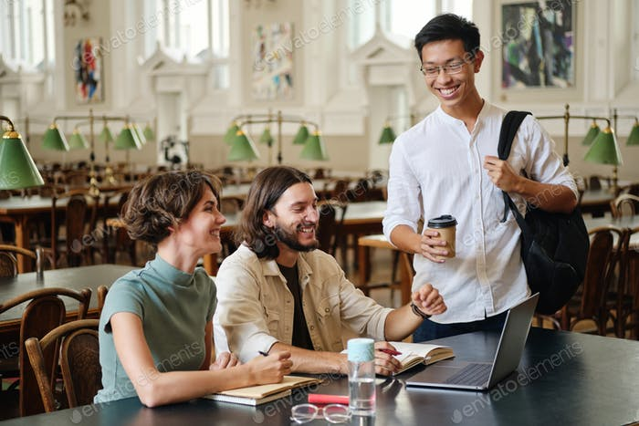 Group of young cheerful students friends joyfully talking studying together in library of university