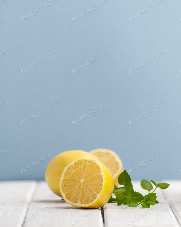 Half a ripe lemon and a mint branch on a white wooden table on a