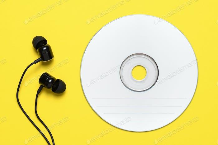 Kompakte Disc und Ohrstöpsel auf gelbem Hintergrund