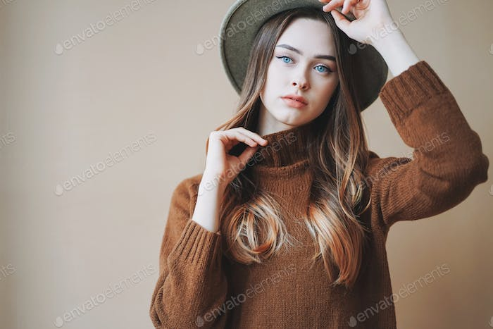 Young beautiful long brown-haired hair girl with blue eyes in brown knitted sweater