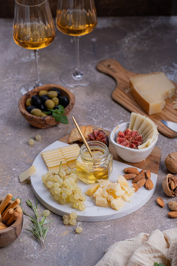 Assorted cheeses on marble plate with figs, nuts, grapes and honey