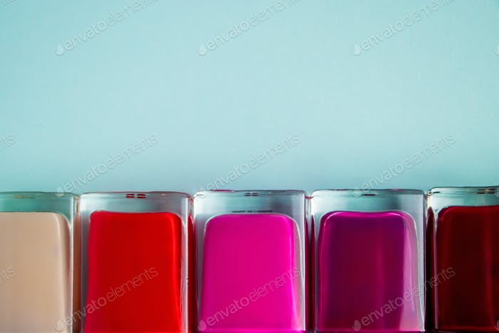 Palette of bright nail polishes on blue background.