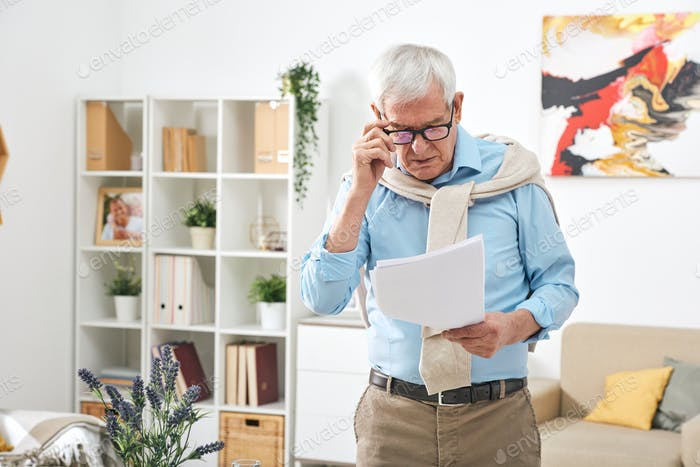 Old male pensioner in eyeglasses and casualwear looking through papers