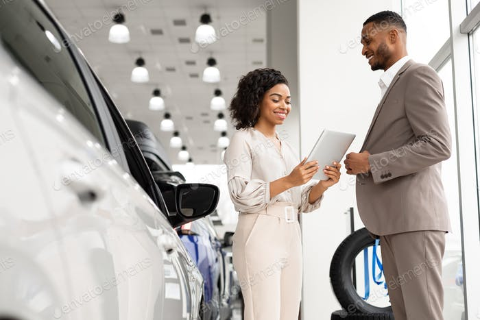 Seller Woman Showing Auto To African Businessman In Dealership Showroom