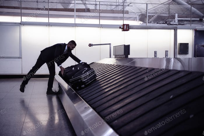 Businessman picking up suitcase on luggage conveyor belt, airpor