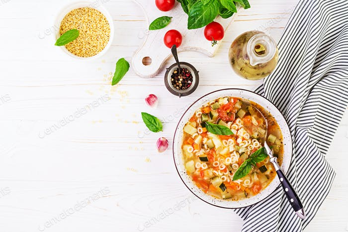 Minestrone, italian vegetable soup with pasta on white table. Vegan soup.  Top view