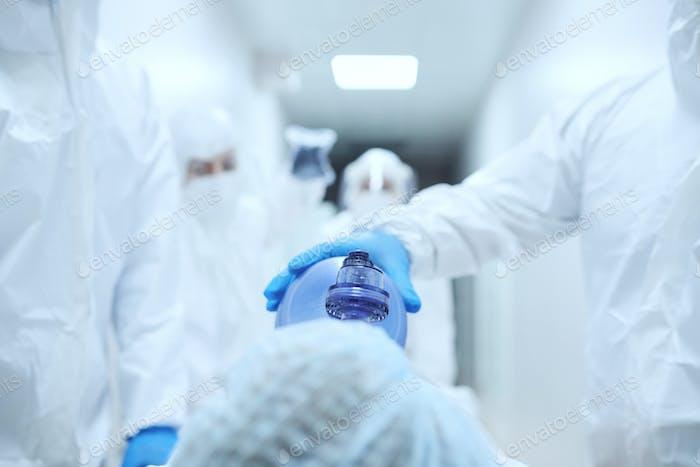 Врач накладывает кислородную маску пациенту