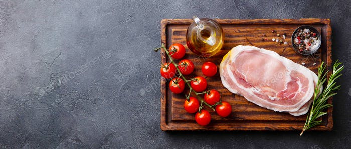 Raw Bacon Slices with herbs, oil and tomatoes on wooden cutting board. Grey background. Top view.