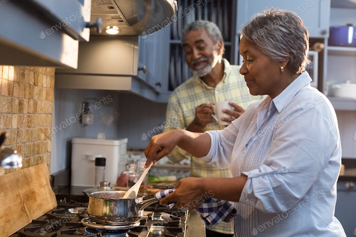 Happy senior couple preparing food home