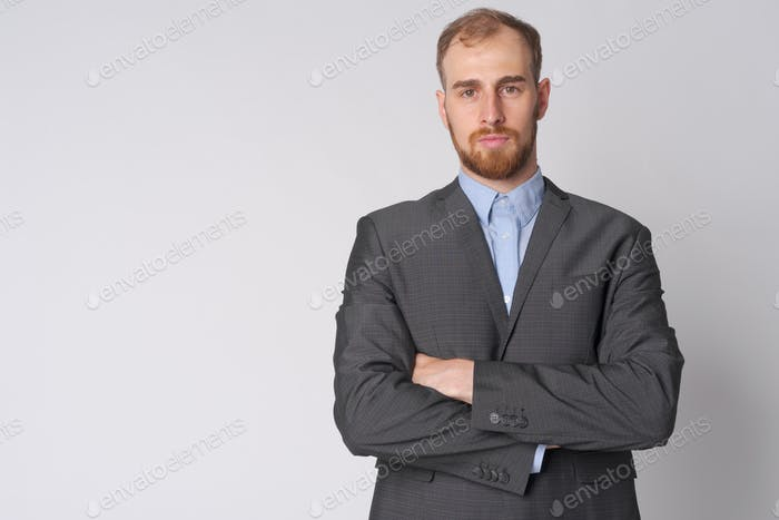 Portrait of young bearded businessman with arms crossed
