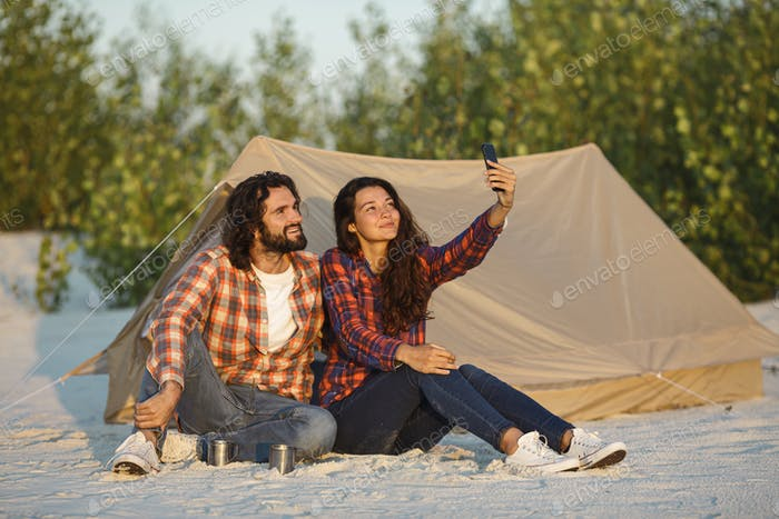 Happy Couple With a Smartphone in the Camp Near the Tent Outdoors