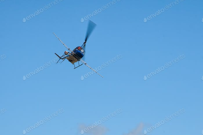 Helicopter is flying in the blue sky. Agricultural work. Transportation aircraft. Spraying fields